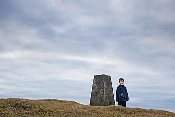 Josh at the trig point on the top of Knock Hill